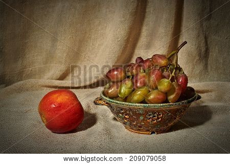 Still life with an apple grapes and a colander on the background of a curtain of coarse cloth. On fruits are drops of water