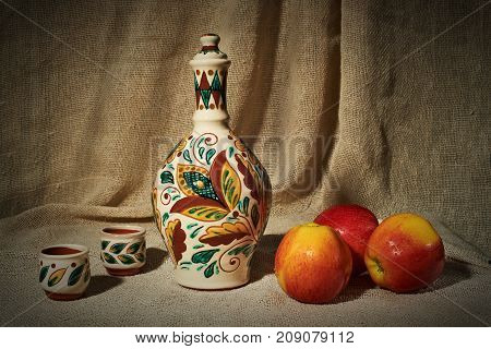 Still life with ceramic handmade bottle and cups as well as apples on the background of a curtain of coarse cloth. On apples are drops of water