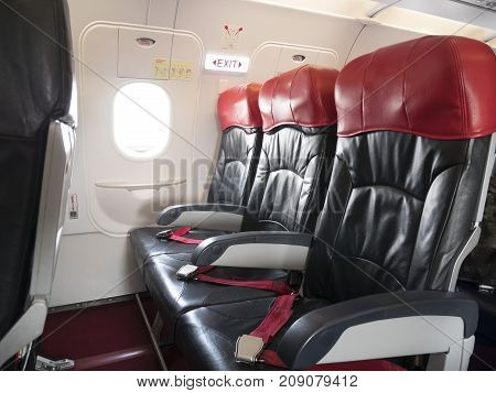Airplane flight safety concept : emergency exit seat row in airplane exit sign light over plane emergency exit door turn on for passenger.