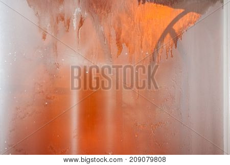 Winter Blurred Background. Frozen Window With Thawing Stains Which Are Flowing Down .