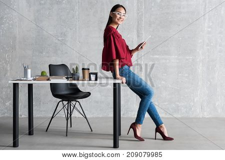 I love my job. Full length portrait of happy young businesswoman using tablet and smiling. She is leaning on table with various office stuff on it. Copy space