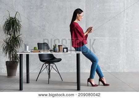 Enjoying modern device. Profile of cheerful stylish young asian woman is holding tablet and looking at screen with smile. She is sitting on desk. Copy space in the left side