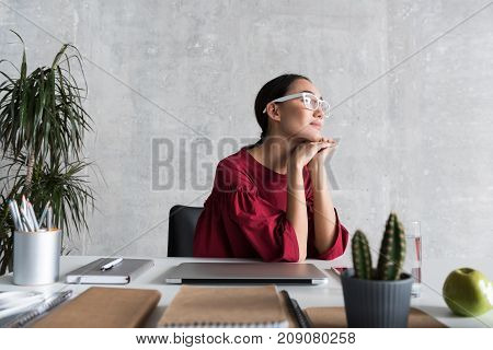 Dreamy sight. Pensive stylish attractive woman is looking aside with expectation while resting in office. She is sitting with elbows on desk and leaning on hands