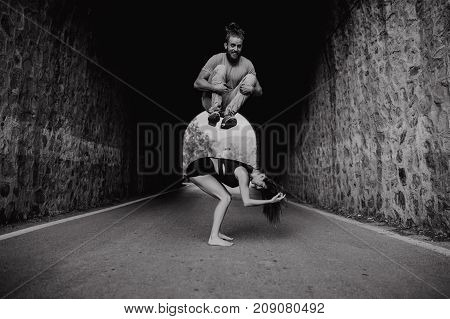 Smiling man jumping over his girlfriend while playing on a road