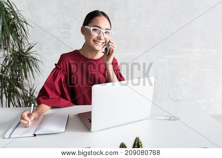 Business issues. Portrait of professional smart asian businesswoman is holding her phone and discussing business while talking with her interlocutor. She is looking at camera with joy. Copy space