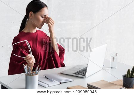 Calm it down. Sad young asian woman is sitting at table with laptop and holding eyeglasses while having headache and working in office. Copy space in the right side