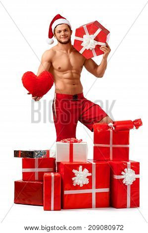 Valentines day is soon to come. Handsome Santa Claus holding a present and a big plush heart isolated on white copyspace on the side