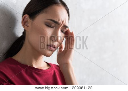 Feeling headache. Close-up of face of young asian woman is in great pain. She is contracting her brow and expressing suffering while leaning on wall and touching her head. Copy space in the right side