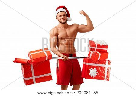 Christmas offer. Toned Santa Claus carrying presents showing his biceps and smiling cheerfully