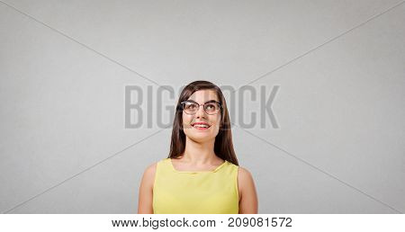 Positive thoughtful girl looking for ideas on a gray background.