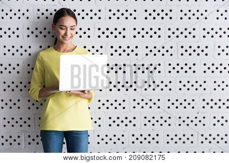 Useful gadget. Cheerful asian girl is standing against brick wall and holding laptop while typing on it with smile. She is expressing gladness while looking at screen. Copy space in the right side