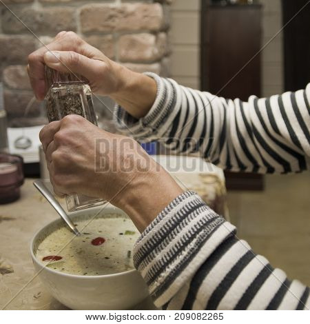 Female hands holding a salt or pepper grinder above a food bowl