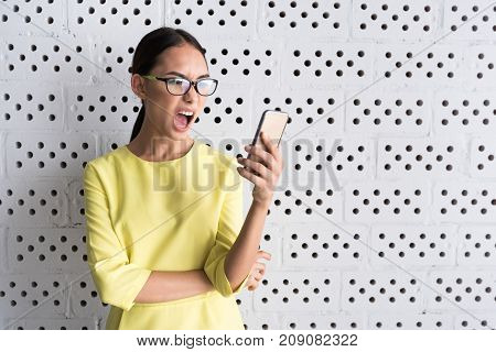 How is it possible. Angry young woman is standing against white wall and holding modern mobile phone. She is expressing annoyed while looking at screen of gadget. Copy space