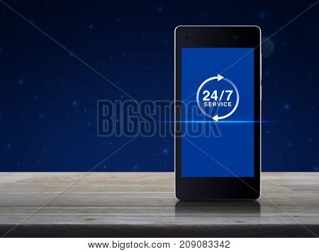24 hours service icon on modern smart phone screen on wooden table over fantasy night sky and moon Full time service concept