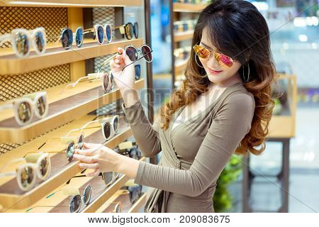 Beautiful young asian woman shopping and select sunglasses fashion with uv protection in optical shop market store