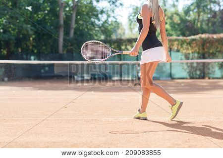 Young woman tennis player move with racket in a tennis court outdoor. Tennis player dressed white skirt, black T-shirt and black cap and waiting for the ball