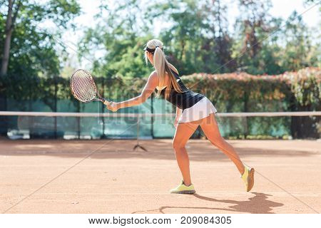 Full body photo of white blonde tennis player in action in a tennis court outdoor. Photo of the lady is made from the back. White woman dressed white shorts, black T-shirt and black cap