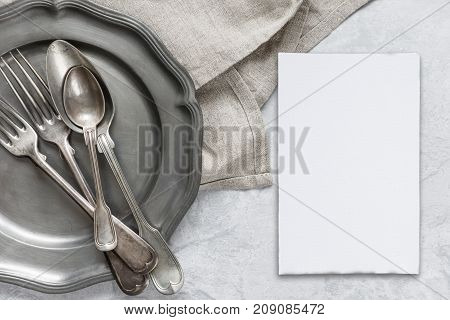 Various silverware on a pewter plate gray flax napkin and white blanc paper card are on the background of gray concrete surface with copy-space