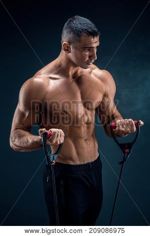 Fitness man exercising with stretching band in studio.