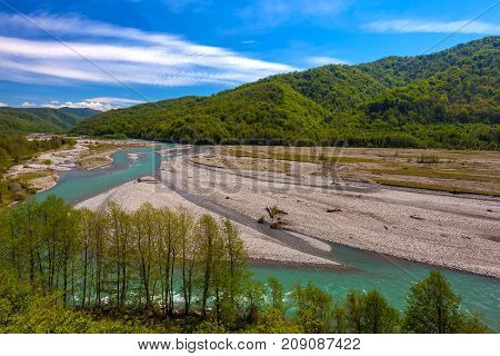 The valley of the mountain river is azure around the forests on the slopes against the background of a clear blue sky. The Shahe River near the village of Bolshoy Kimchay, Sochi.