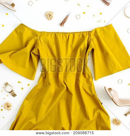 Women's fashion clothes and accessories on white background. Flat lay female golden styled look with dress high heels watch bracelet. Top view.