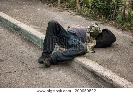 Drunk person lying outdoors. Unconscious man in the street. Shocking alcohol statistics.