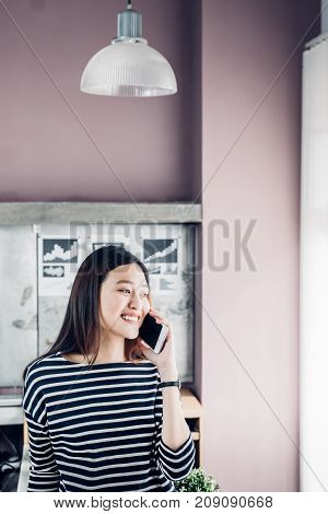 Asia businesswoman owner wear casual cloth talking on mobile phone in home office working space for contact customeroffice lifestyle with technology