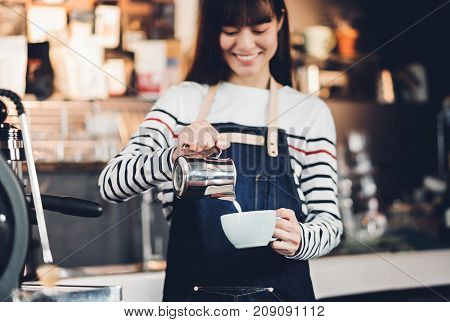 Asia woman barista pour milk into hot coffee cup at counter bar in front of machine in cafe restaurantFood business owner concept