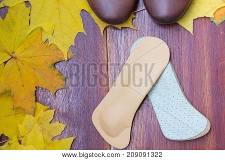 Brown Shoes With Orthopedic Insoles. Autumnal Background, Maple Leaves On A Wooden Board