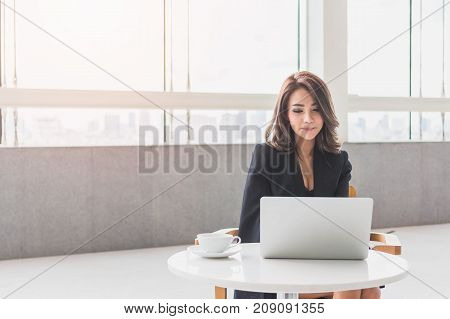 Beautiful young Asian girl working at a office space with a laptop. Concept of smart female business.Vintage tone