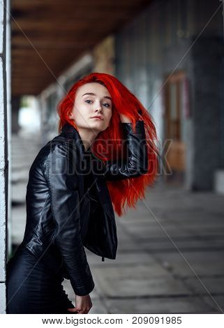 Closeup portrait of a redhead in a dark leather clothes holding her magnificent hair in urban background. Punk Unformal street style