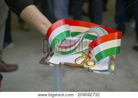 Ribbon with Italian flag in a scissor tray used for institutional ceremonies as inauguration of new projects and activities. Cutting of the ribbon.