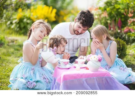 Father playing tea party game with his three adorable daughters. Having many children single father. Loving and caring father. Single parent. Beautiful decorated tea party outdoors at the backyard. male babysitter sitter childminder sitter-in.