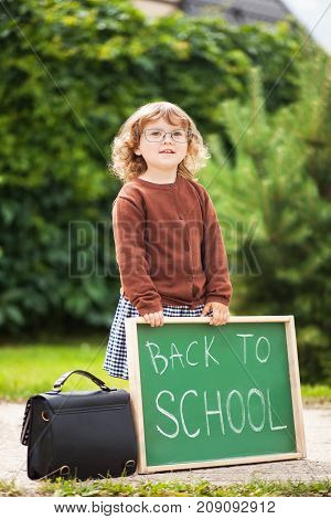 Cute toddler girl wearing glasses and school uniform with back to school blackboard. Fall outdoors education concept sunny autumn day. Early education little genius wunderkind concept.