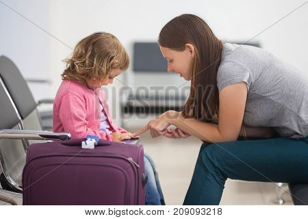 Adorable toddler girl and her mom waiting at the airport with luggage traveling with children family vacation time at the waiting room.