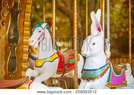 Old French carousel in a holiday park. Horses and rabbits on a traditional fairground vintage carousel. Merry-go-round.