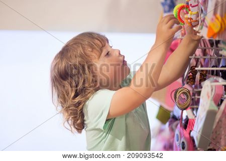 Adorable toddler girl in baby apparel store buying bijouterie.