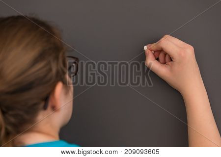 A close up of a teacher's hand about to write on the chalkboard