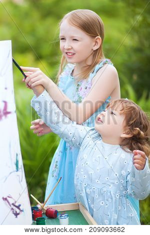 Sisters painting together in a beautiful garden smiling and laughing. Sisters relationships sister friendship. Older sister helps toddler girl teaching painting.