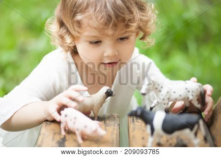 Cute toddler girl playing with farm animal figures outdoors. Summer leisure. Childhood on countryside. Child learning farm animals. Early education and developement.