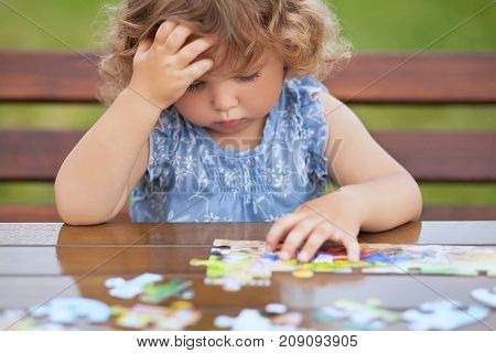 Blonde unhappy toddler girl solving puzzle on a table hard Difficult task. Early education and developement. Little genius concept. Emotional.