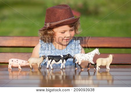 Cute toddler girl playing with farm animal figures outdoors. Summer leisure. Childhood on countryside. Child learning farm animals. Early education and developement. Role-playing with animals.