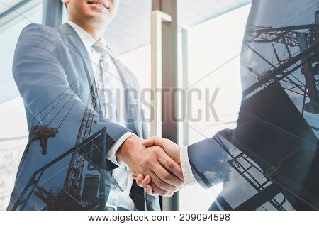 Double exposure of two businessmen reaching an agreement and making handshake with abstract construction site - Greeting and dealing real estate business concepts.