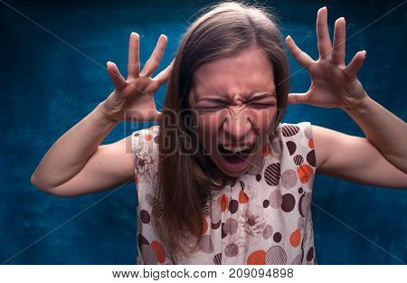 Angry caucasian woman shouting. Portrait of frustrated young female on blue background. Studio shot.