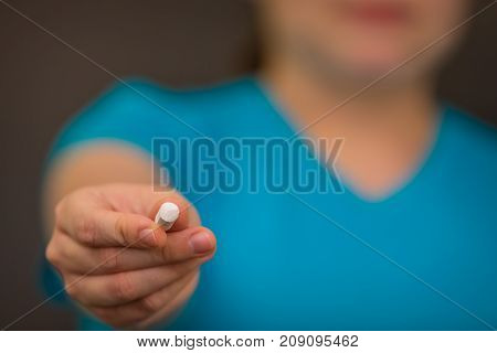 A teacher holding out a small piece of chalk