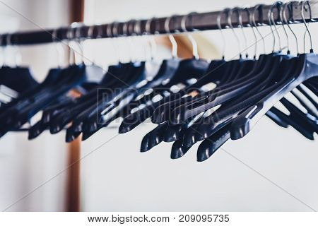 Empty Wardrobe Stand With Black Hangers At Business Event Venue.