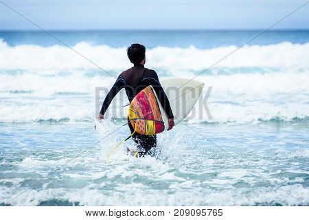 Surfer guy with surfboard in hand running towards big waves. Man in surfing wet suit is running in the waves of cold atlantic ocean in Galicia Spain.