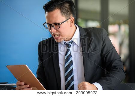 Asian angry businessman wearing glasses white shirt black suit necktie look at tablet and get disappointed after checking bad news. Screaming at monitor on work table with copy space for text.