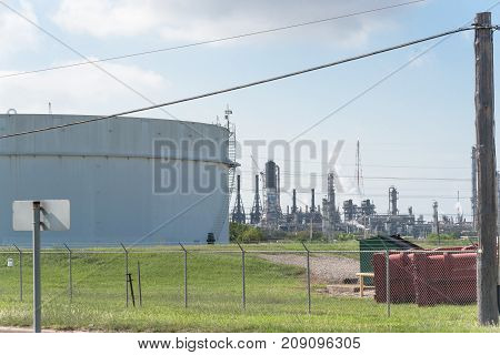 Oil tanks and oil refinery under blue sky in Pasadena, Texas, USA. Large white industrial tank for petrol, oil, natural gas storage at petrochemical, oil refinery plant. Energy and power background
