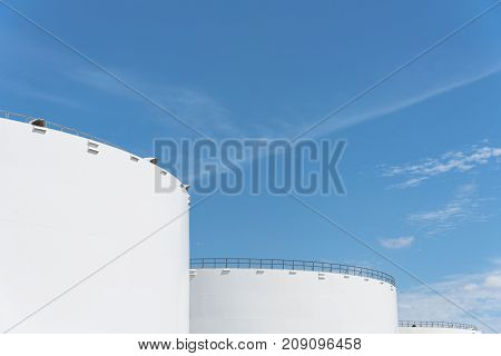 Oil tanks in a row under blue sky in Pasadena, Texas, USA. Large white industrial tank for petrol, oil, natural gas storage. Tank farm at petrochemical, oil refinery plant. Energy and power background